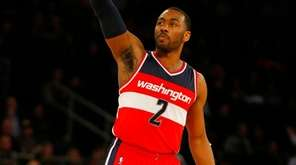 John Wall of the Wizards follows through on a three-point