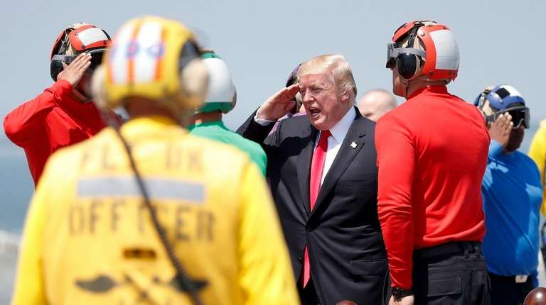 President Donald Trump salutes as he boards Marine