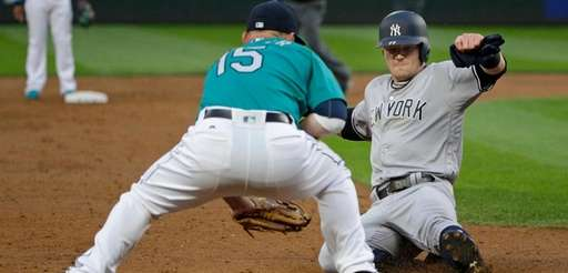 The Yankees' Clint Frazier slides safely into third