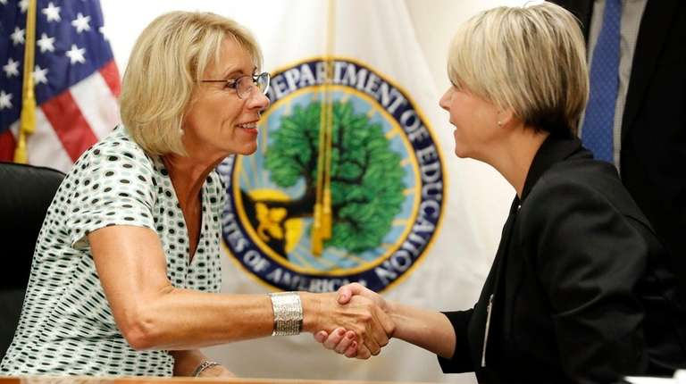 Education Secretary Betsy DeVos, left, meets recently with