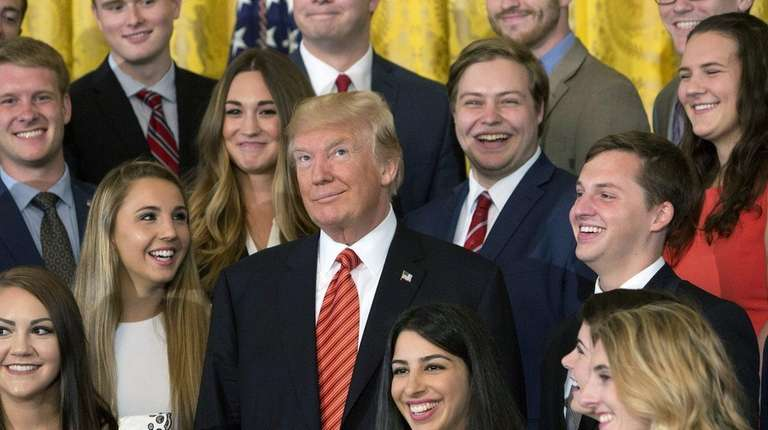 President Donald Trump poses for photographs with a