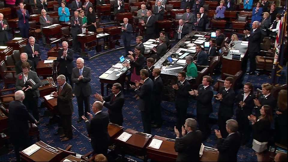 McCain arrives in the Senate Chamber to applause on Tuesday, July 25, 2017.
