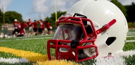 A football helmet lies on the ground.