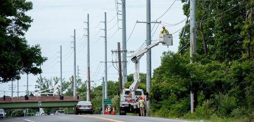 Contractors work on new PSEG poles that were