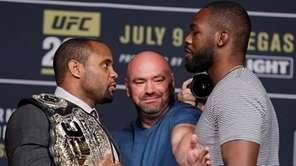 Dana White, center, stands between Daniel Cormier, left,