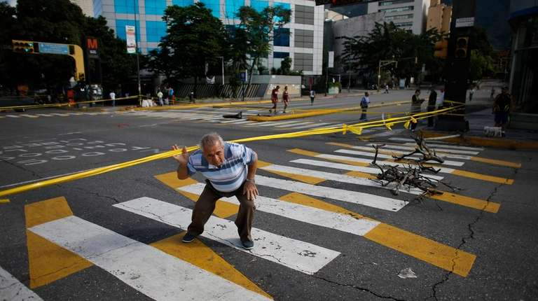 A pedestrian ducks under yellow tape strung up