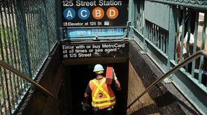 An MTA worker enters a Harlem subway