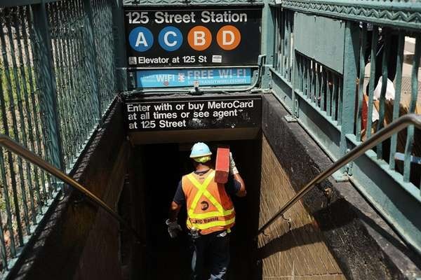 An MTA worker enters a Harlem subway