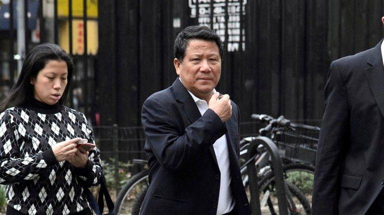Chinese billionaire Ng Lap Seng, center, heading to