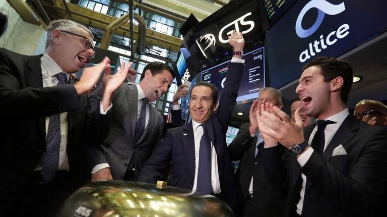 Altice founder Patrick Drahi, center, is applauded as