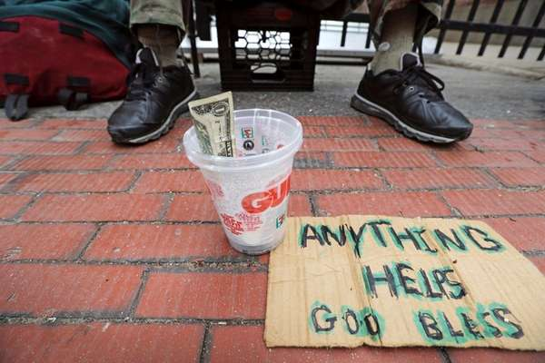 D. Rogers, a homeless man, panhandles for change