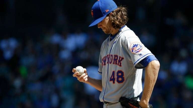 Mets pitcher Jacob deGrom looks at the ball