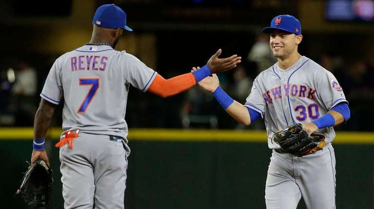 The Mets' Michael Conforto, right, greets Jose Reyes