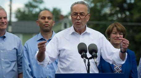 Sen. Chuck Schumer, accompanied by Congressional Democrats, speaks