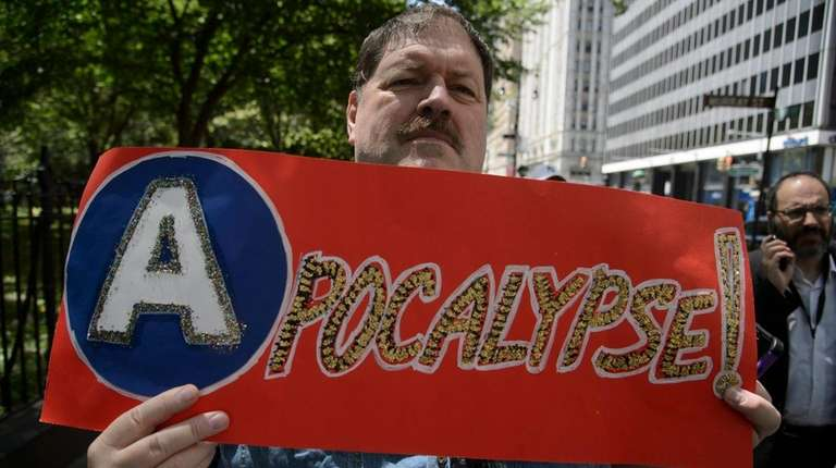 Subway-rider advocate David Kelso holds a sign Monday,