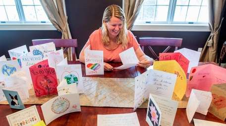 Lori Lang, of Malverne, with cards she's collected,