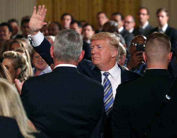 President Donald Trump waves to the crowd while