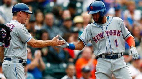 Mets third base coach Glenn Sherlock, left, congratulates