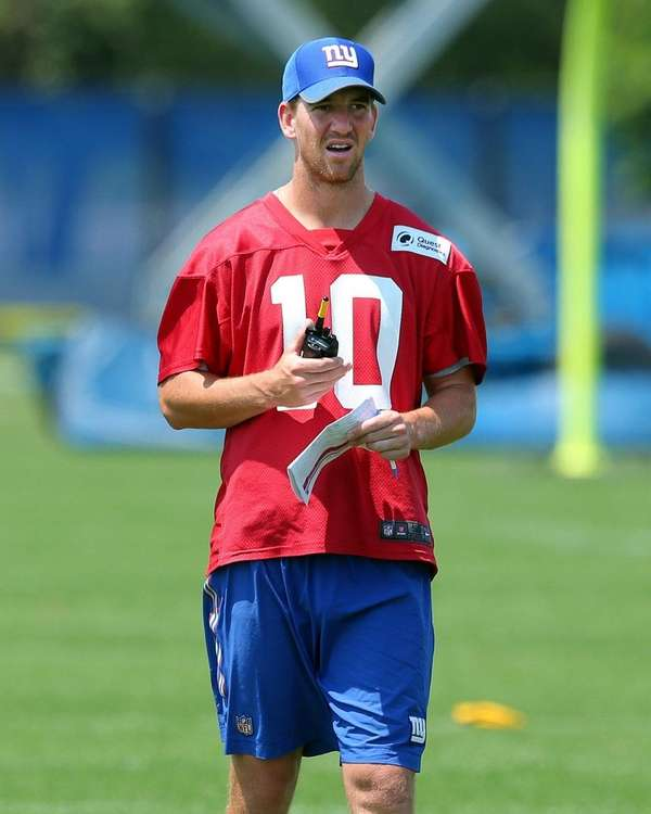 Giants quarterback Eli Manningwatches practice from the sidelines