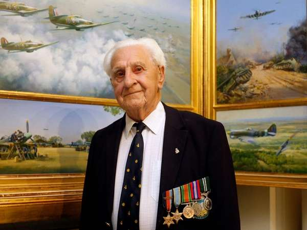 Ken Wilkinson poses by paintings of Spitfires in