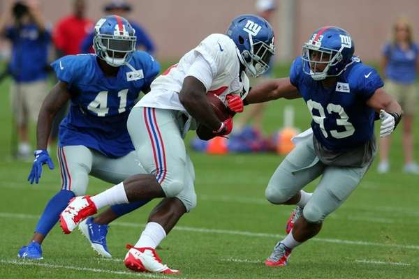 Giants linebacker B.J. Goodson , right, catches up with