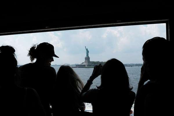 People look out at the Statue of Liberty