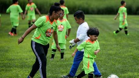 Johanna Vasquez, an instructor at Futgol-Fast Soccer, helps