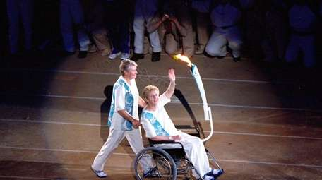 Torchbearers Betty Cuthbert is pushed by Raelene Boyle