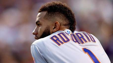 Mets shortstop Amed Rosario watches from the dugout in