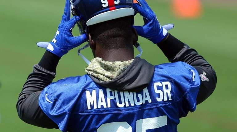 Giants defensive end Stansly Maponga Sr.puts on his