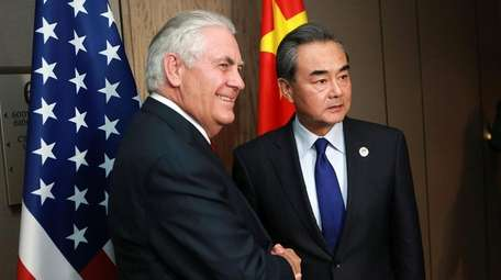 Secretary of State Rex Tillerson (L) shakes hands