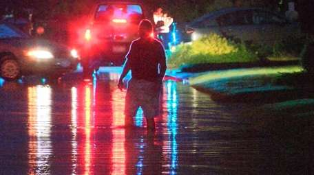 A man wades through an area flooded by