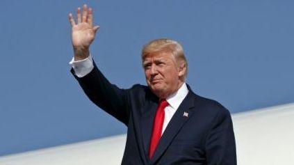 President Donald Trump waves as he walks down