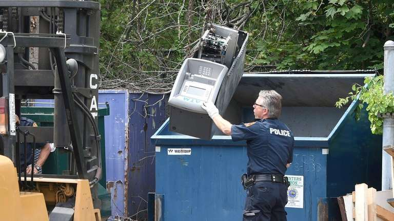 Suffolk County police remove an ATM that was