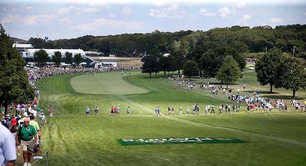 Spectators line and cross the first fairway in