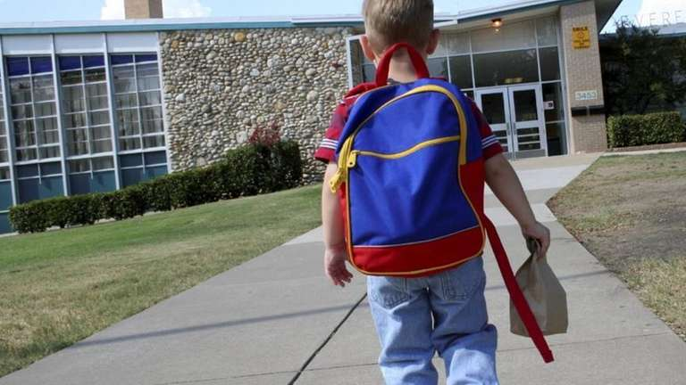 A child walking into kindergarten.