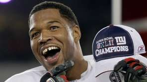 Michael Strahan celebrates after the Giants beat the Patriots