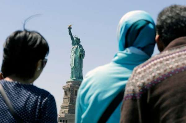 People look at the Statue of Liberty from
