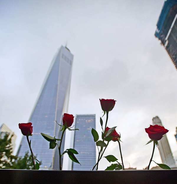 Flowers are placed by the names of victims