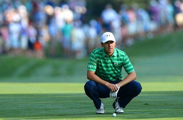 Jordan Spieth crouches near his ball on the