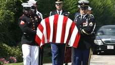 An honor guard carries the coffin of Sen.