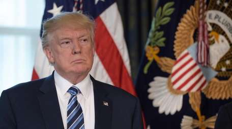 President Donald Trump listens as Treasury Secretary Steven