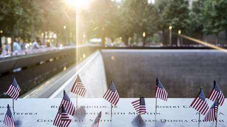 American flags are placed on the 9/11 Memorial