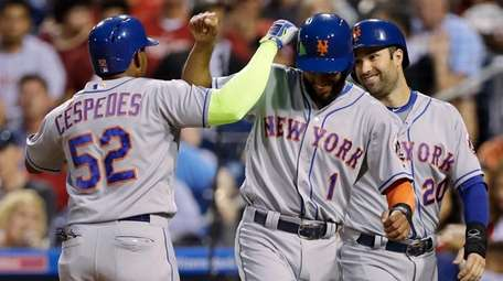 The Mets' Yoenis Cespedes, left, Amed Rosario, center,