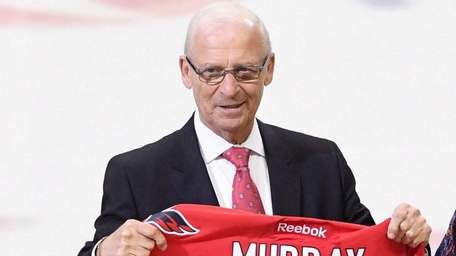 Bryan Murray holds a signed Capitals jersey as
