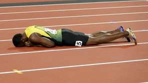 Jamaica's Usain Bolt lies on the track after