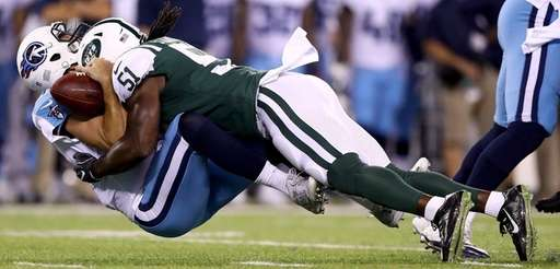 Alex Tanney of the Titans is sacked by