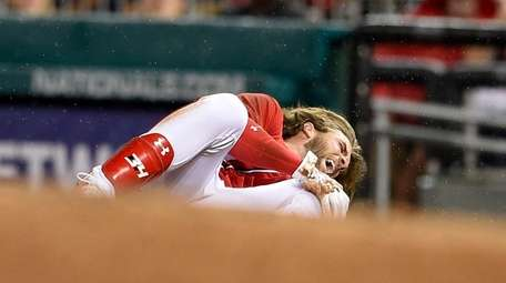 The Nationals' Bryce Harper grabs his knee after