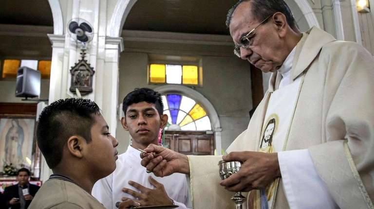 A youth takes the Eucharist from Msgr. José