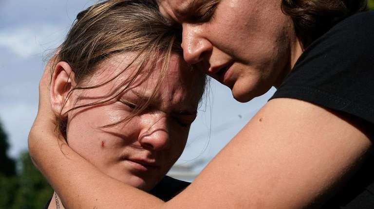 Jessica Mink, right, embraces Nicole Jones during a